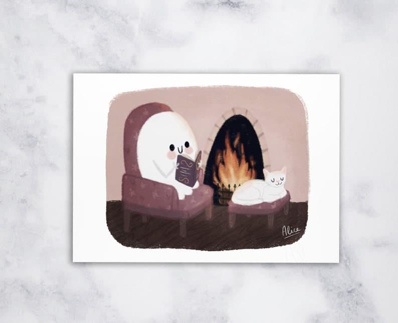 Carte Halloween - Ghosty et son chat lisant près du feu
